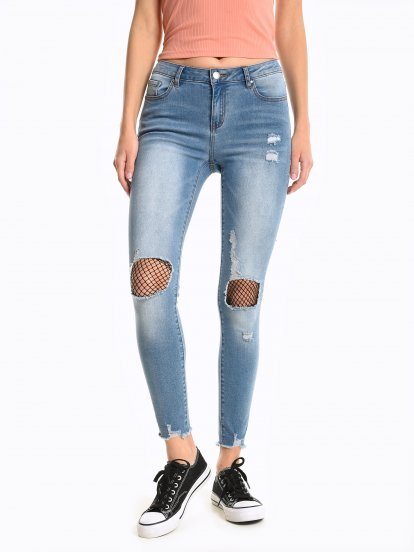 Distressed skinny jeans with fishnet