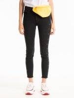 Skinny jeans with metal eyelets